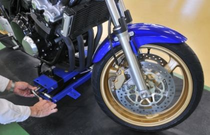 blue motorcyce in a jack with hand